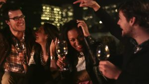 2634556-stock-footage-a-group-of-friends-hang-out-on-a-rooftop-bar-at-night-and-dance-and-laugh-around-the-fireplace
